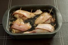 Coloque as coxas na assadeira envoltas em bacon