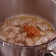 Frite e cozinhe o frango, junte tomate concentrado